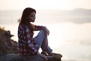 Young woman sitting outside ready to learn how to detox safely.
