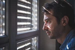 Man staring through blinds suffering painkiller addiction symptoms