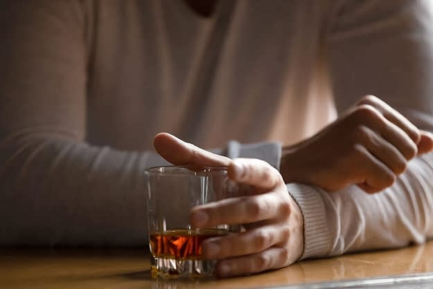 a male holding a glass of alcohol thinking about how to stop alcohol addiction