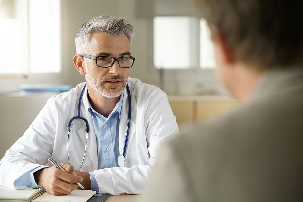 Therapist explains medication assisted treatment for opioid addiction to his client
