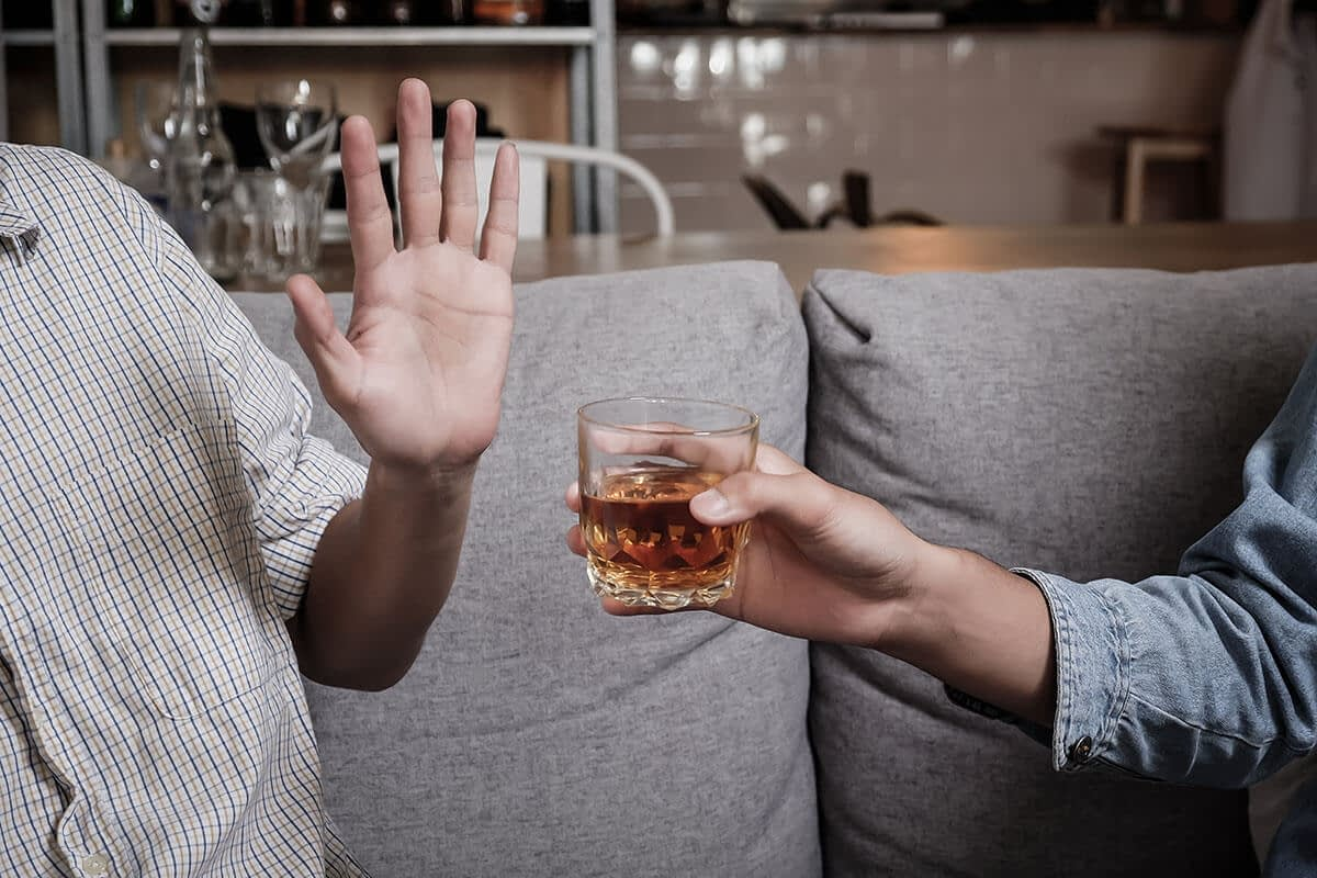 a man refuses a drink as he wonders how can i stop drinking