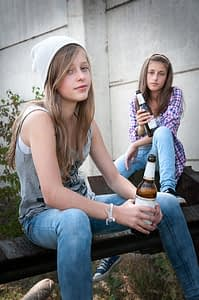 two girls sitting on step exhibit Teen Alcohol Abuse while drinking beer