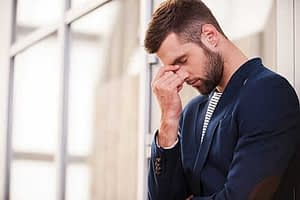 A man clutches the bridge of his nose thinking about how he might need mood disorder treatment