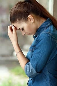 A woman looks down resting her forehead on her hand as she goes through painkiller withdrawal symptoms