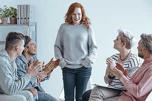 Five young adults participate in group therapy activities