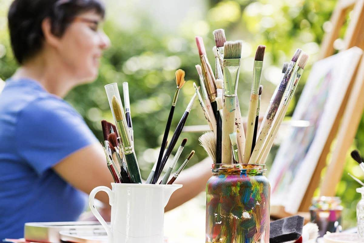 woman painting on easel getting the benefits of art therapy in recovery