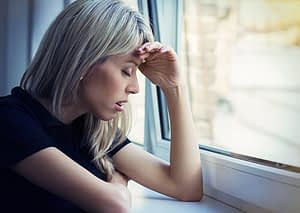 sick woman by window has Heroin Withdrawal Symptoms