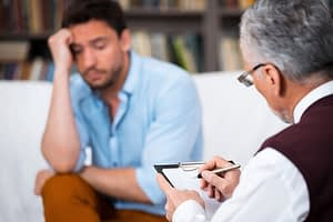 man undergoes trauma focused cognitive behavioral therapy at therapist's office