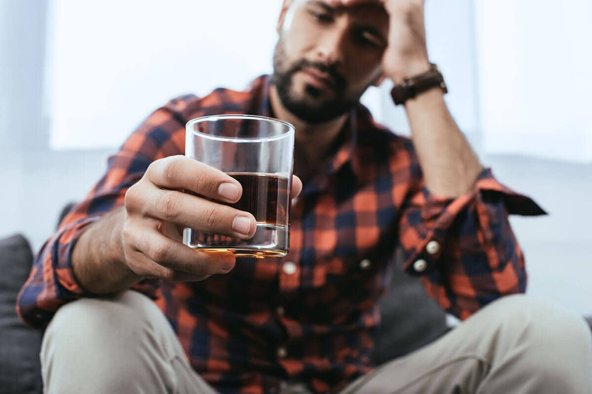 young man holds a glass of liquor as he wonders if he is developing an alcohol dependence