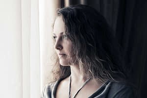 woman looking out window wonders why do people do drugs