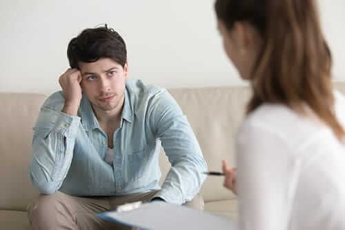 A female therapist explains behavioral therapies for drug abuse to a male patient