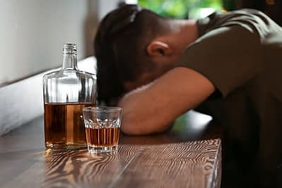 man with whiskey bottle wonders how to quit drinking