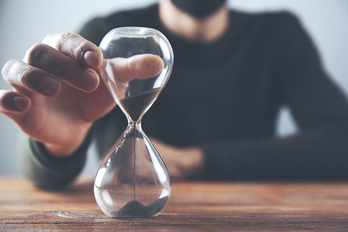 man using hourglass to practice patience