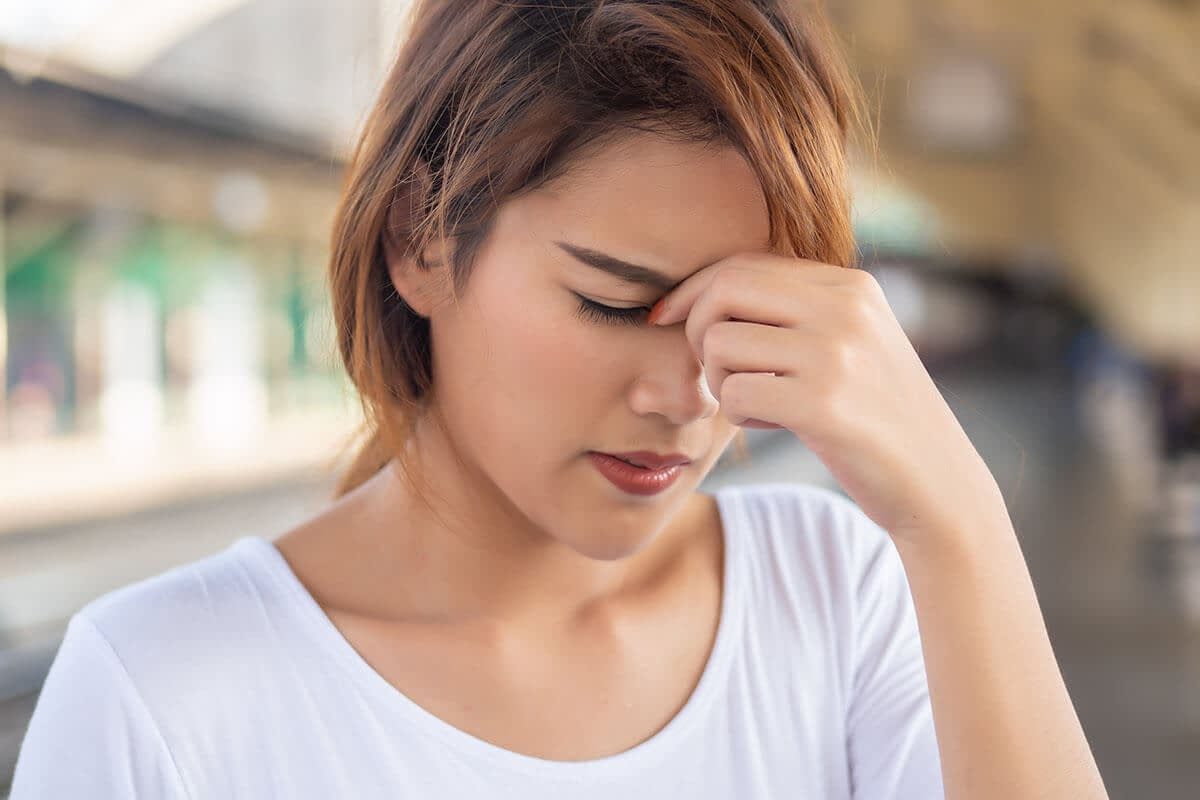 a woman holds her head as she debates oxycodone vs hydrocodone treatment