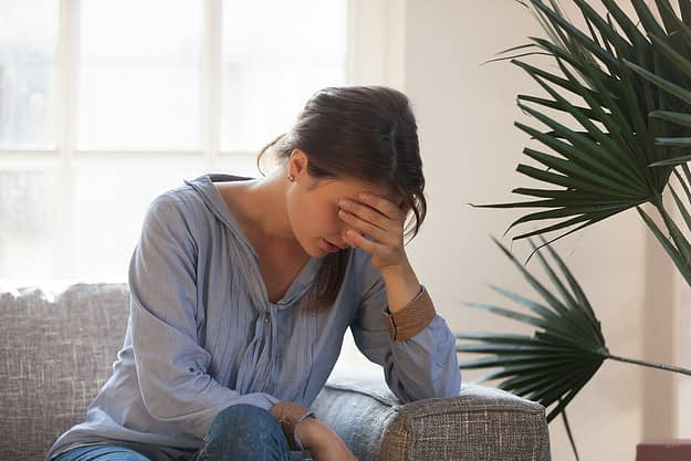 a woman holds her head in her hand as she considers the relapse definition
