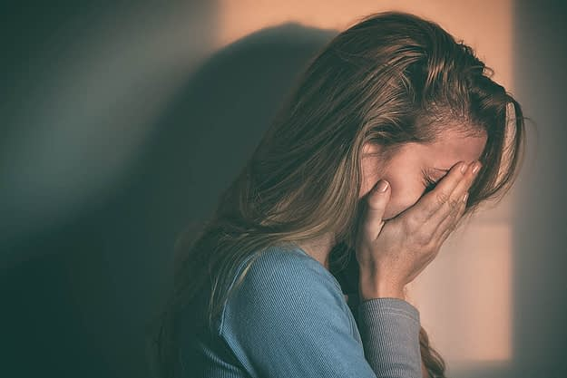 young woman with her hands over her face thinking about her signs of addiction
