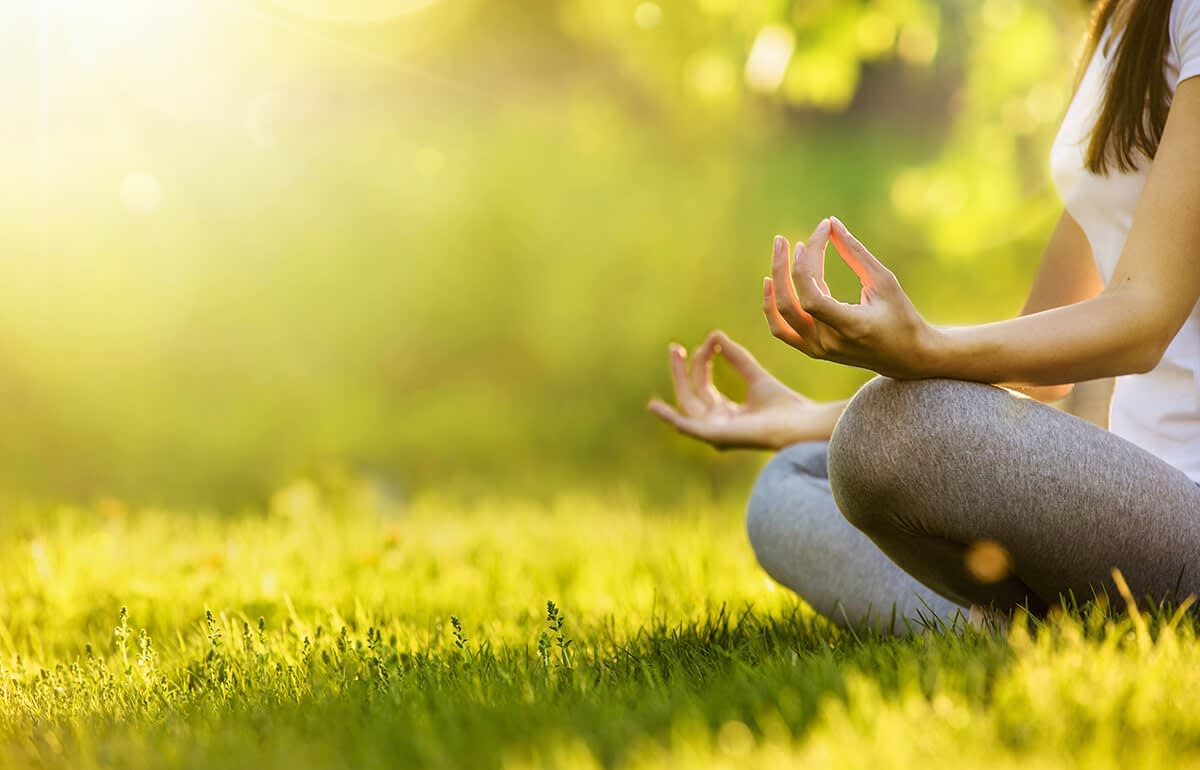 a woman meditating in a field during holistic healing methods