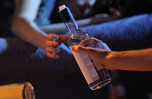woman handing off bottle displays alcoholic behavior