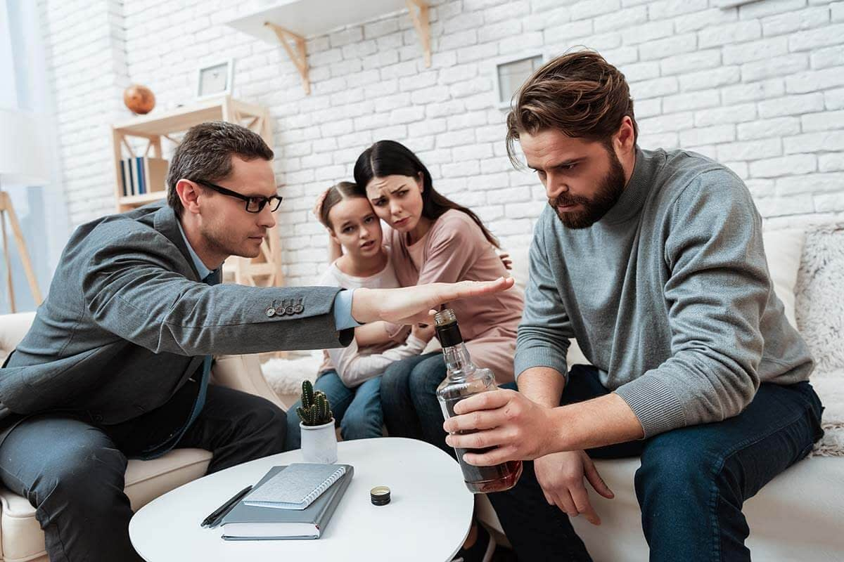 Family learning what are process addictions during therapy as man stops husband from drinking