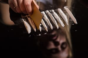 person doing lines on mirror suffers from cocaine effects