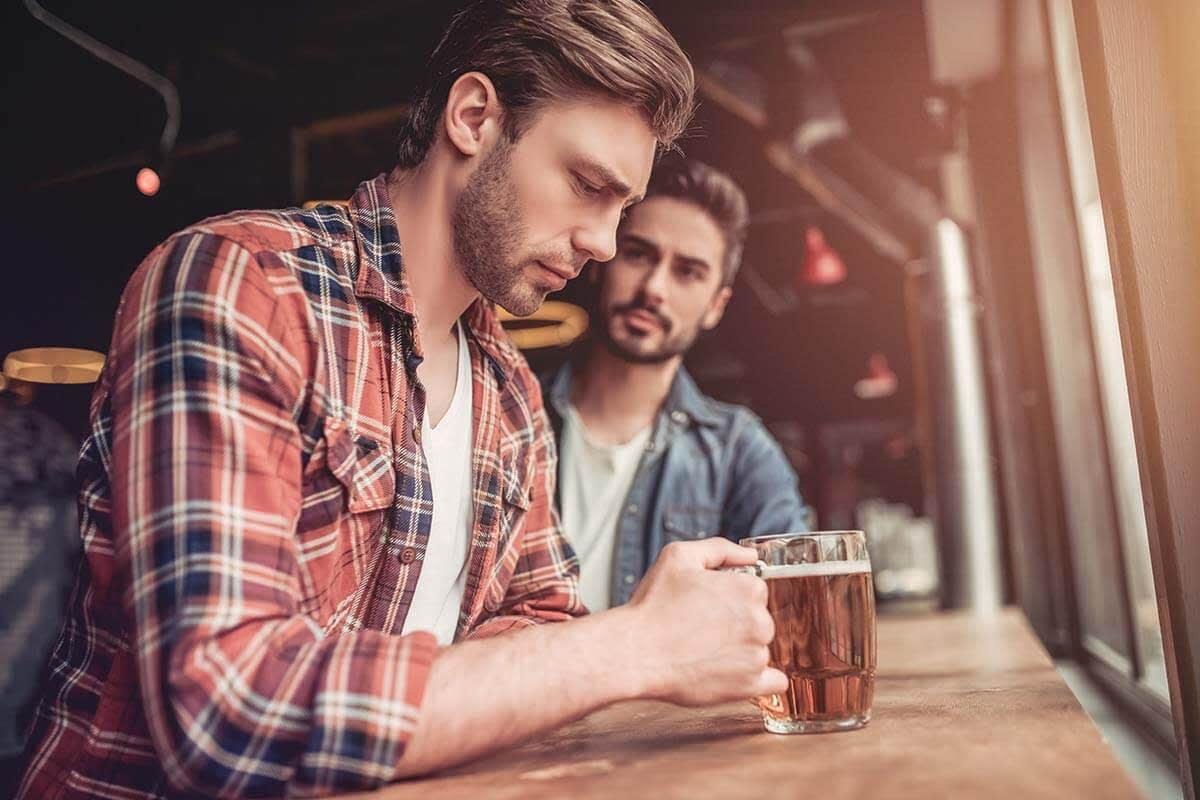 man sitting with friend getting help for an alcohol addiction