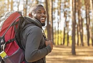 man smiling and backpacking through the woods near drug rehab center near Bellevue, Washington