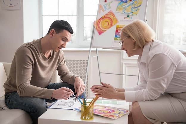 man showing art therapy work to therapist during art therapy for addiction treatment in Oregon