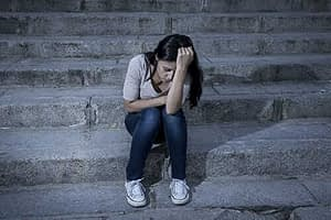 woman sitting on stairs suffers crystal meth effects