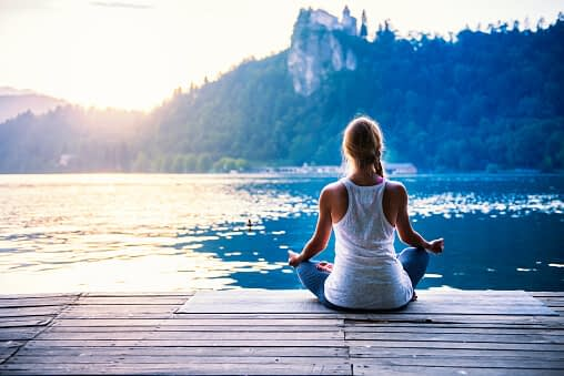 woman practicing mindfulness meditation mindfulness therapy by the lake