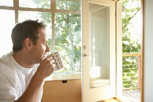 man drinks coffee and looks out window during extended care addiction treatment program