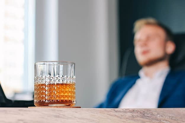 man sitting in front of a glass of alcohol during Alcohol Awareness Month