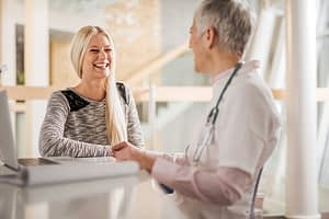 woman laughing with medical professional at Partial Hospitalization Program center