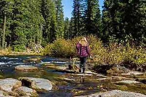 woman standing on rocks near a lake at Grants Pass Alcohol Rehab Center