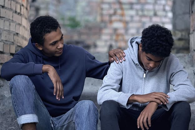 a man puts his hand on his son's shoulder as they discuss alcohol addiction signs in teens