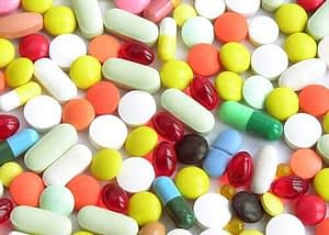 A table covered in many colors of pills represents many different types of amphetamines