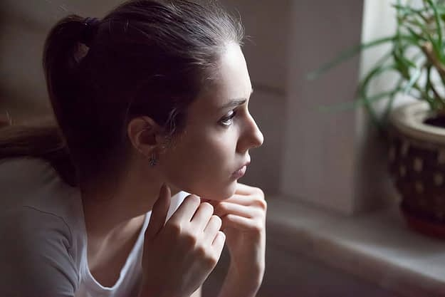 young woman sitting at home thinking about relapse prevention techniques