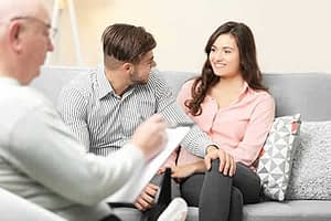 A male counselor discusses family therapy activities with a young couple