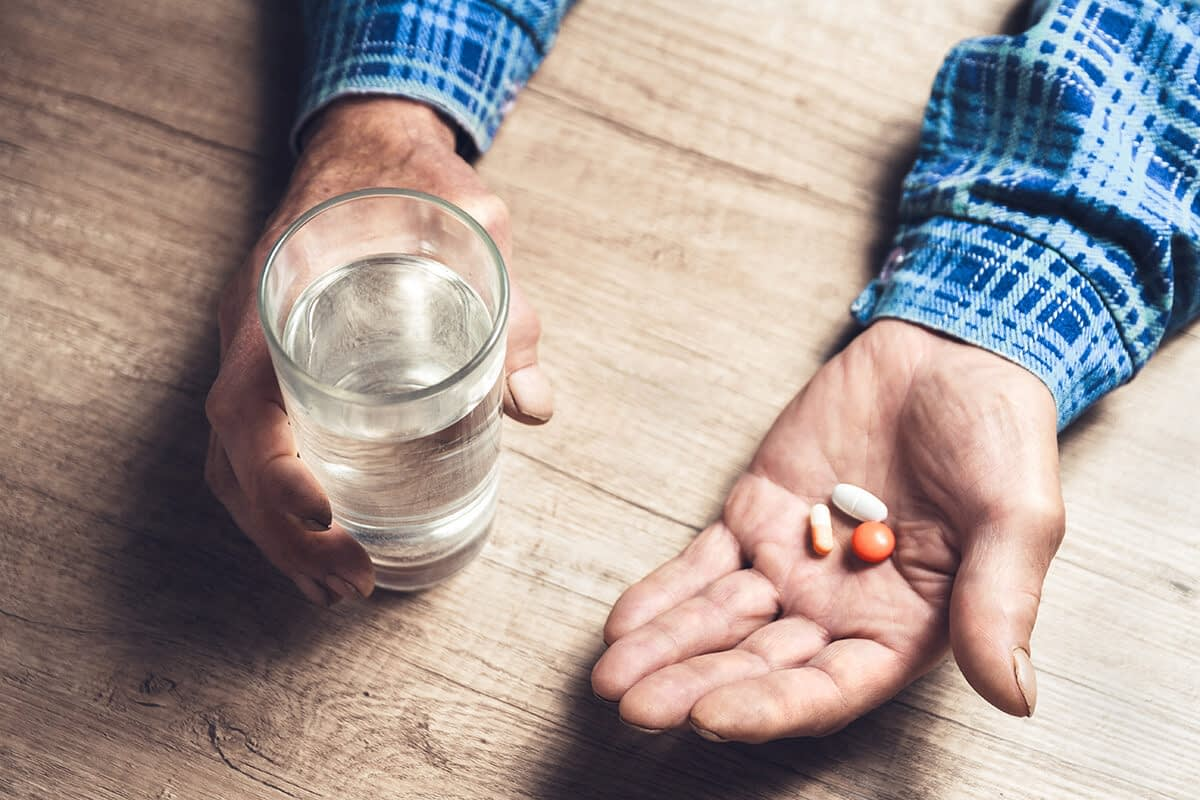 a man holds water and pills and thinks about drug misuse