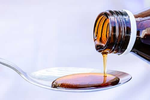 Cough syrup is poured into a spoon in an amount that would not be able to give you a dextromethorphan high