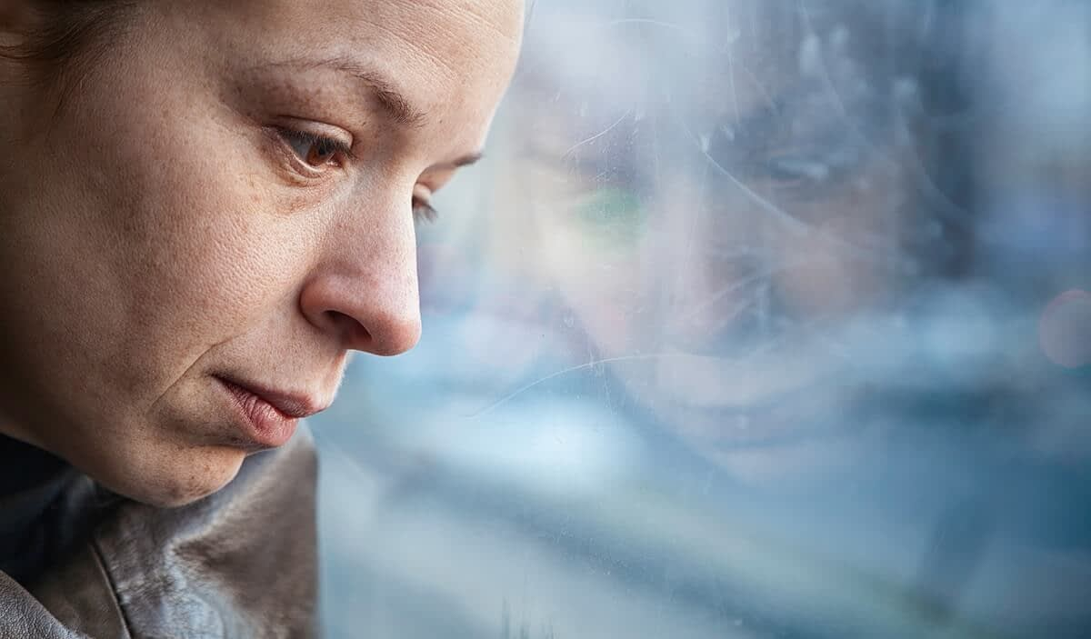 Woman looking out the window wondering what causes addiction