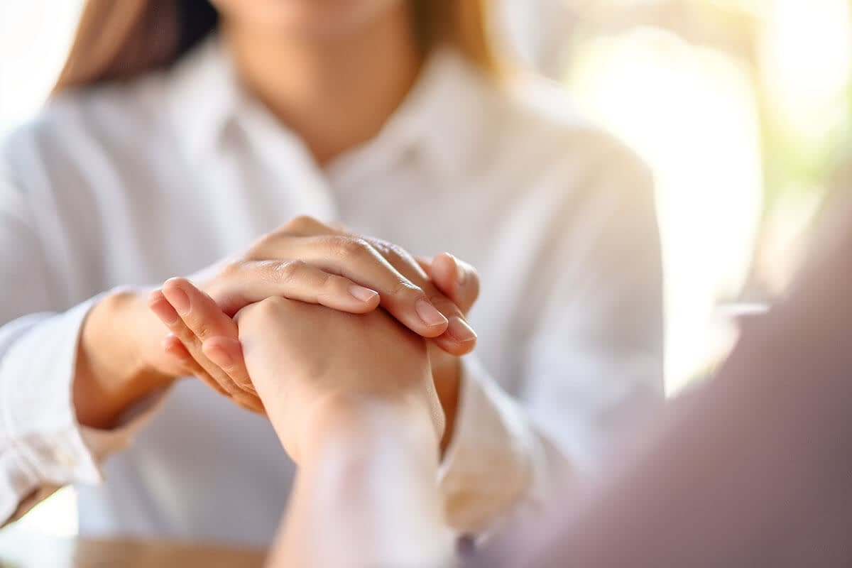 a therapist holds a client's hand as she tells him how to help an addict recover