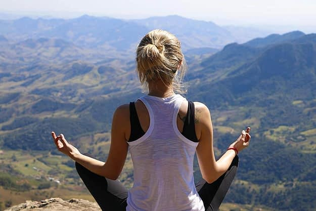woman sitting atop a mountain is feeling the benefits of mediation