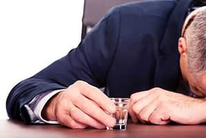 man with shot glass and head on table needs help for alcohol addiction