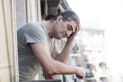 A middle aged man leans out a window wondering what is a depressant