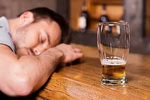 A man passed out on a bar possibly suffering from alcohol poisoning