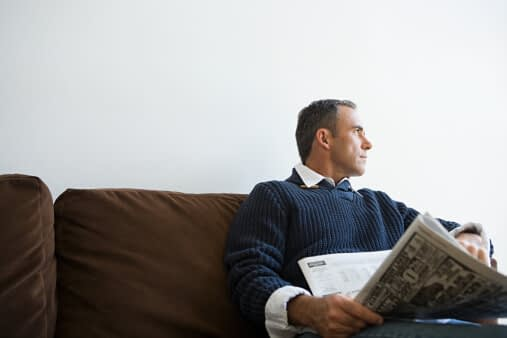 a man sits on a couch at an intensive outpatient program for substance abuse and reads the newspaper