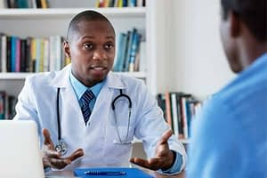 doctor speaking with patient in office about drug treatment programs