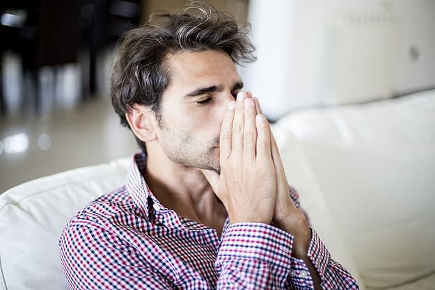 a man folds his hands in front of his face as he thinks about the substance abuse definition
