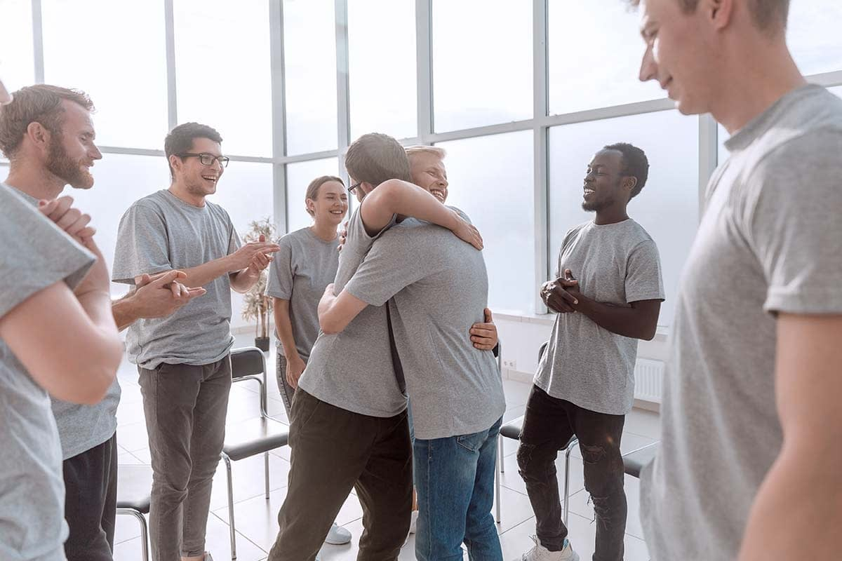 two men hugging during group therapy for addiction treatment to get the benefits of group therapy
