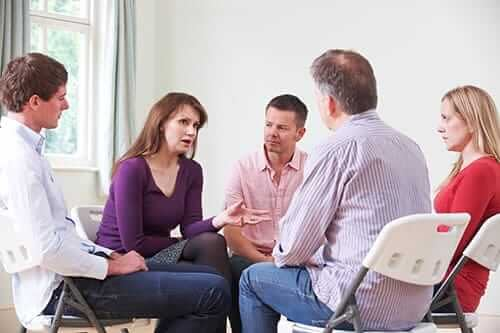 A counselor explains substance abuse group topics to a therapy group